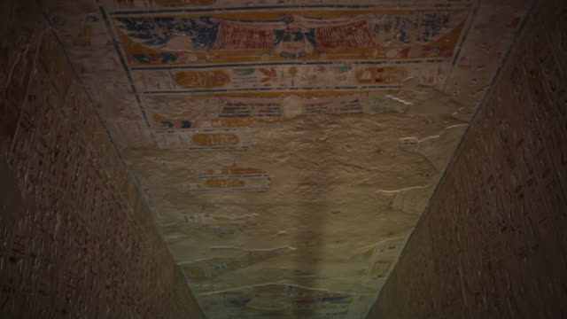 Tourist walk inside an Ancient Egyptian tomb Located in the 'Valley of the Kings' Tilt down
