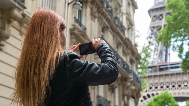 Tourist walking the streets of Paris, taking pictures of Eiffel Tower