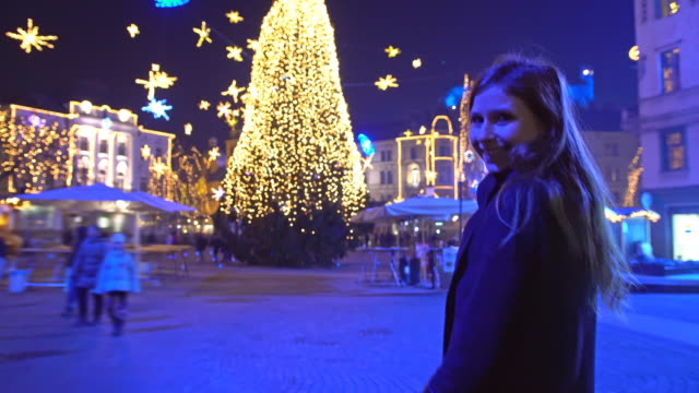 Tourist walking towards christmas tree in town square