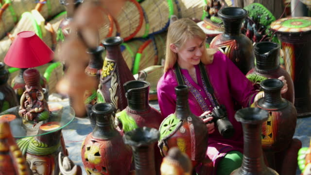 Tourist watching a collection of vase in the fair, Suraj Kund, Faridabad, Haryana, India