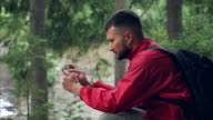 Tourist with beard using phone to navigate in forest