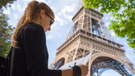 Tourist with map of Paris standing under Eiffel Tower