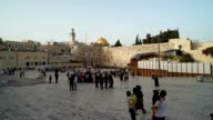 Tourists and visitors walk to the Wailing Wall