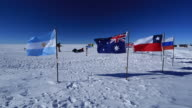 Tourists at magnetic South Pole (unrecognizable), various national flags