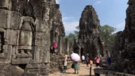 Tourists between Apsara relief and giant stone face tower of Bayon temple