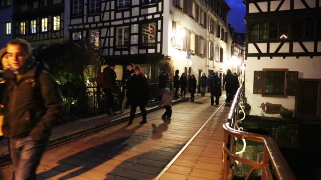 Tourists cross a small pedestrian bridge