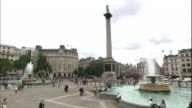 Tourists cross Trafalgar Square near a fountain.