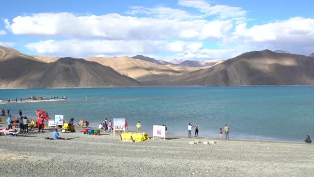Tourists enjoying the good weather and the breathtaking Himalayas around Pangong Lake, Ladakh, India