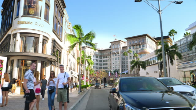 Tourists explore Rodeo Drive in Beverly Hills luxury landmark, Los Angeles, California, 4K