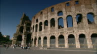 Tourists gaze at the arches lining Rome's ancient Colosseum.