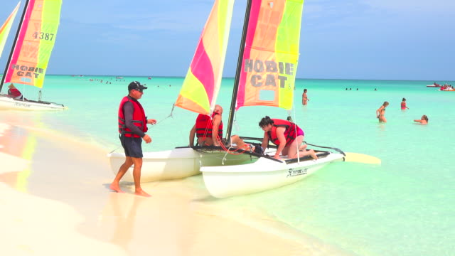 Tourists get on board a 'catamaran' with vivid color sails that highly contrast with the transparent crystalline water of the famous travel...