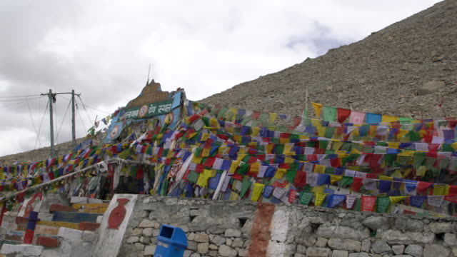 Tourists having fun around the yellow sign board and prayer flags at the Chang La Pass, Ladakh, India