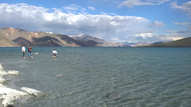 Tourists having fun into the cold waters of Pangong Lake in the Himalayas, Ladakh, India