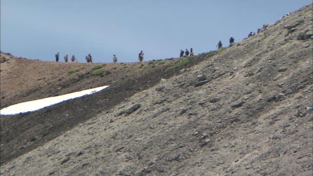 Tourists hike along a ridge on Mt. Norikura in Japan.