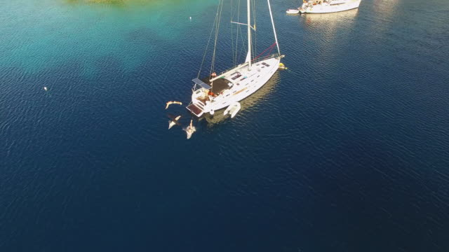 AERIAL Tourists jumping into the sea off a sailboat