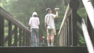 Tourists on a footbridge film Zen Goro Falls as they are covered in mist.
