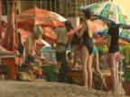 Tourists on beach putting up umbrellas on windy day Goa
