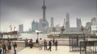 Tourists on The Bund gaze at the Shanghai skyline across the Yangtze River.