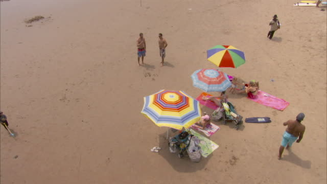 Tourists relax under colorful umbrellas. Available in HD