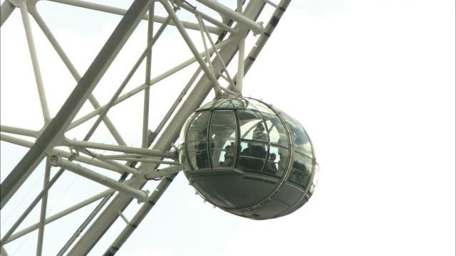 Tourists ride the London Eye.