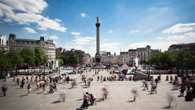 Tourists scurry through Trafalgar Square in London.