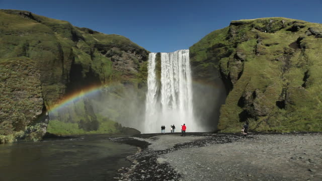 WS Tourists standing in front of Skogafoss waterfall and rainbow glowing / HOF, Vestur-Skaftafellssysla, Iceland