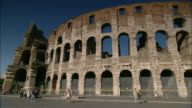 Tourists stroll along the exterior perimeter of Rome's ancient Colosseum.
