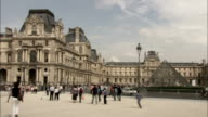 Tourists stroll past the Louvre in Paris. Available in HD.