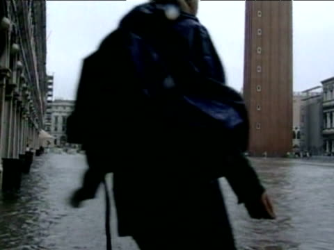 Tourists struggle to walk across flooded piazza in bad weather Venice 17 Jul 02