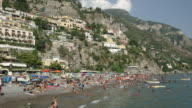 Tourists sunbathe on a beach in Positano during the summer holidays.
