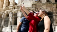 Tourists taking a selfie in front of the Coliseum, Rome