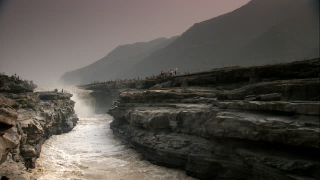 Tourists view the raging Yellow River flowing through a ravine in China.