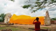 Tourists visit buddha statue and take a photo