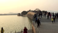 Tourists visit the SeventeenArch Bridge in the Summer Palace on March 4 2017 in Beijing China