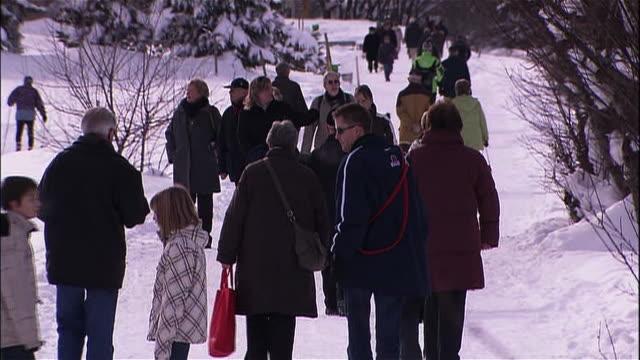 Tourists walk along a snowy path.