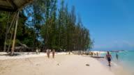 Tourists walk along the beach on Phi Phi Island