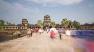 TL, WS Tourists walk along the causeway at the main entrance of Angkor Wat temple / Siem Reap, Cambodia
