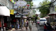 Tourists walk in a street with shops in traveller quarter Banglampoo