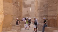 Tourists walk near pillars of the Great Hypostyle Hall at The Karnak Temple Complex
