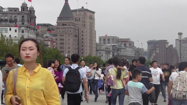 Tourists walk next to the river at the Bund in Shanghai
