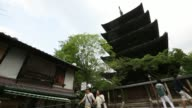 Tourists walk past a five story pagoda at a temple in Kyoto Japan on Saturday May 3 Tourists look out from the verandah known as Kiyomizu Stage at...