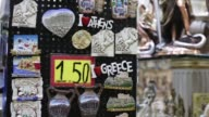 Tourists walk past a sovenir shop in Athens Greece on Tuesday December 6 gvs of souvenirs and magnets