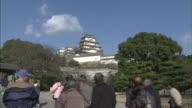Tourists walk toward Himeji Castle in Japan.