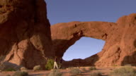 Tourists walking in front of South Window Arch at golden hour - wide