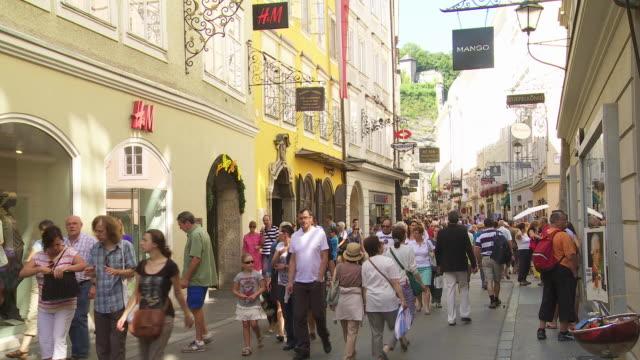 Tourists Walking in Getreidegasse (Grain Lane) in Salzburg and Passing the Birthplace of Wolfgang Amadeus Mozart