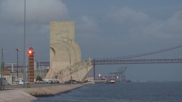 WS Tourists walking near Monument to the Discoveries along Tagus River at base of April 25th Bridge / Lisbon, Portugal