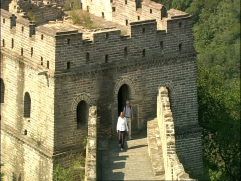 Tourists walking out from watch tower and along Great Wall of China, Mutianyu, China