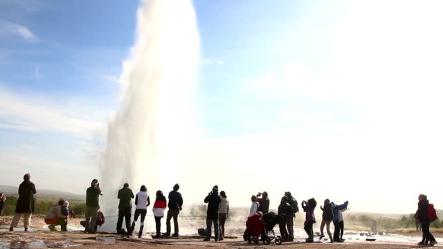 Tourists watching the Strokkur geyser eruption in Iceland at dusk