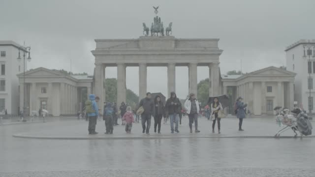 Tourists wearing waterproof coats and using umbrellas in the rain at the Brandenburg Gate in Berlin Germany on Wednesday July 26 2017