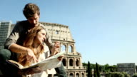 Tourists with guide and map in front of the Coliseum